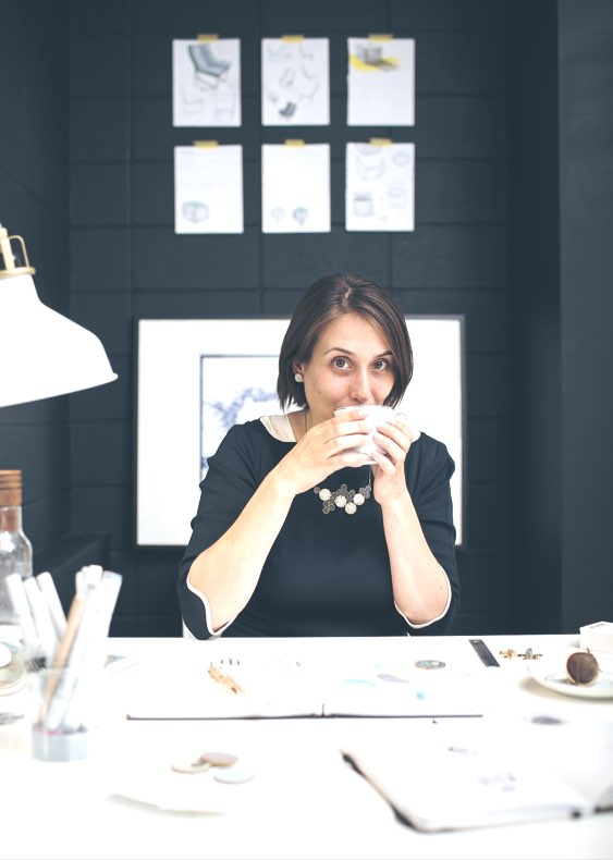 One of three images in a row with Amanad Nogier wearing a black dress and one of her necklaces on. Amanada is sitting at her desk in front of a blurred out black cinderblock wall with her sketches taped up. In this version, she is drinking from a tea cup looking at the camera.